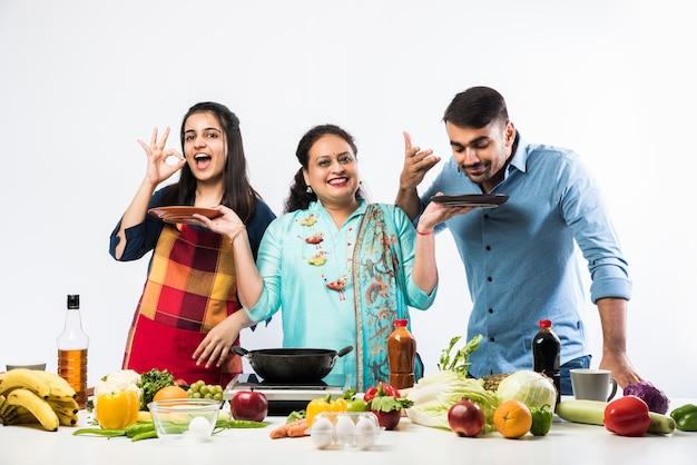Indiano madre o sorella attiva che si prende cura del figlio e della figlia in cucina