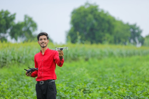 Agronomo indiano che tiene drone e telecomando in mano al campo agricolo