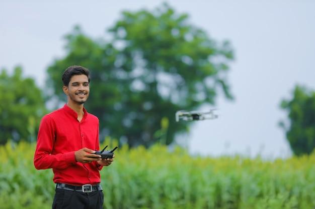 Agronomo indiano utilizzando drone in campo agricolo