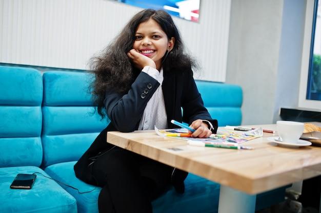 La donna dell'artista indiano indossa un'immagine formale della pittura e ascolta musica indù dagli auricolari, mentre è seduto al bar.
