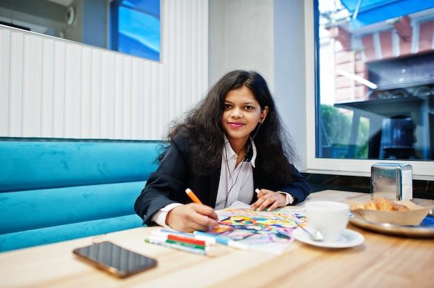 La donna dell'artista indiano indossa un'immagine formale della pittura e ascolta la musica indù dagli auricolari