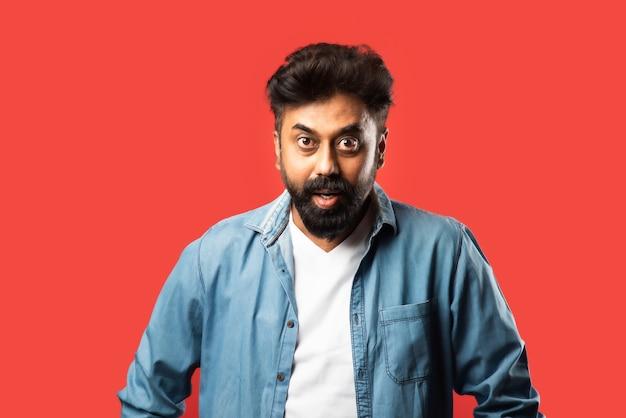 Uomo barbuto asiatico indiano con sguardi sorpresi o wow, in piedi sul rosso