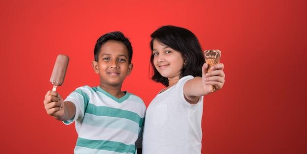 Bambini carini indiani o asiatici che mangiano gelato o barretta di mango o caramelle. isolato su sfondo colorato