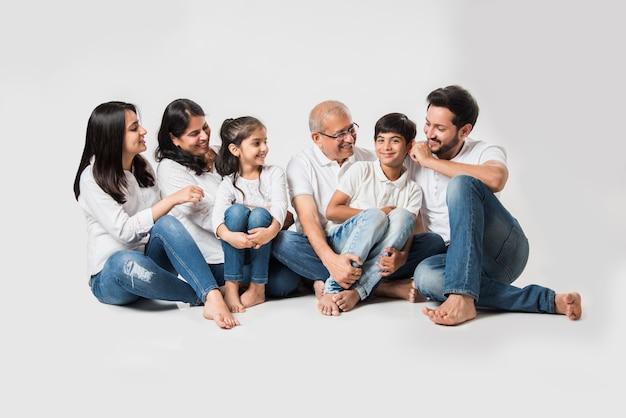 Famiglia asiatica indiana che si siede sopra fondo bianco. coppia senior e giovane con bambini che indossano jeans blu e top bianco. messa a fuoco selettiva
