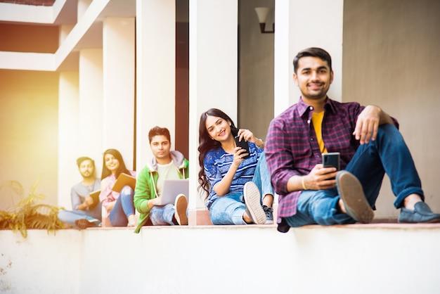 Gruppo asiatico indiano di studenti universitari che utilizzano smartphone per social media, sms, guardare video