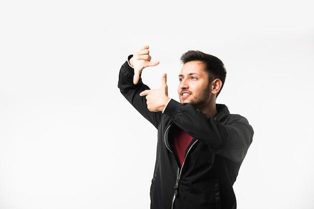 Uomo asiatico indiano che fa una cornice usando le mani e le dita, cercando di trovare una buona vista perfetta, isolata su sfondo bianco