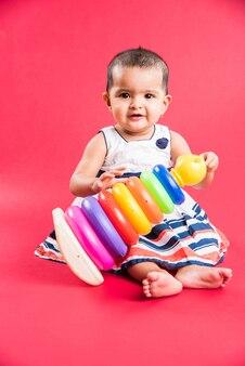 Bambino indiano o asiatico o neonato o bambino che gioca con giocattoli o blocchi mentre è sdraiato o seduto isolato su uno sfondo luminoso o colorato