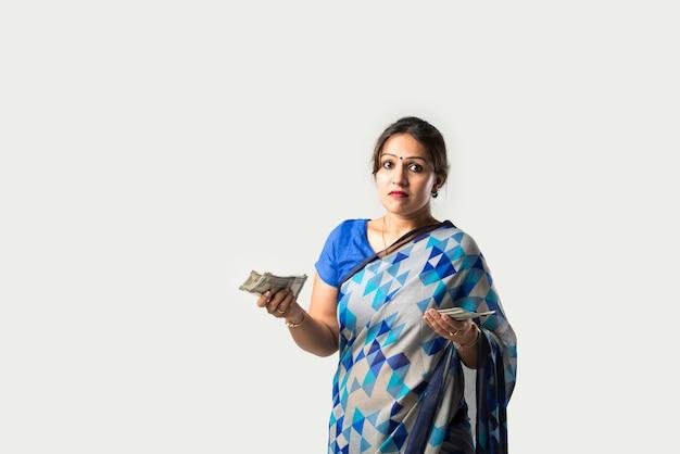 Donna asiatica indiana in sari o sari che mostra o tiene in mano banconote di carta o ventaglio di denaro contro il muro bianco