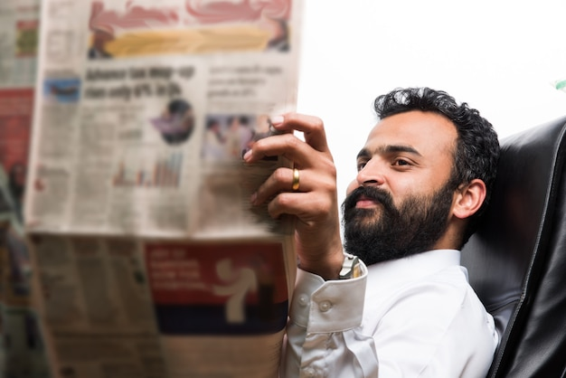 Giovane uomo d'affari asiatico indiano che legge il giornale mentre beve un caffè alla scrivania dell'ufficio