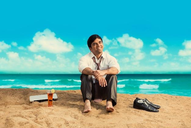 Giovane uomo d'affari asiatico indiano che si rilassa o lavora dalla spiaggia godendosi una pausa dal lavoro