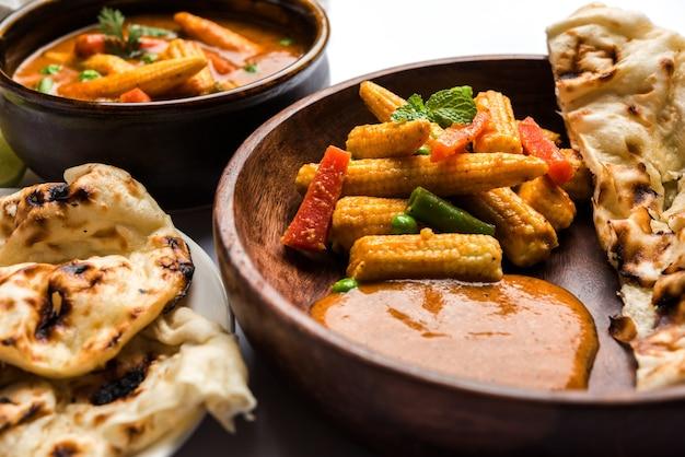 Indian baby corn masala curry preparato in salsa rossa servito con roti/naan o pane indiano. su sfondo lunatico. messa a fuoco selettiva