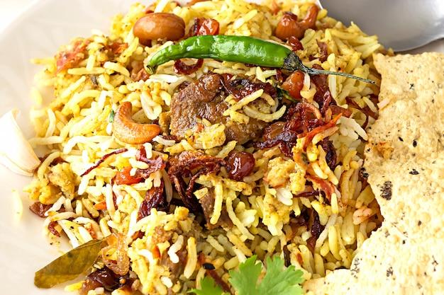 Biryani indiano con contorno e peperoncino