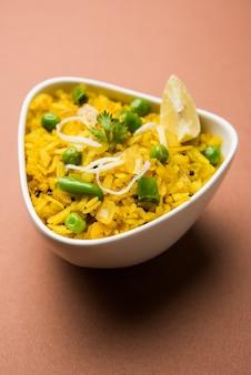 Piatto da colazione indiano poha conosciuto anche come pohe o aalu poha composto da riso battuto o riso appiattito. i fiocchi di riso sono leggermente fritti in olio con spezie serviti con tè caldo
