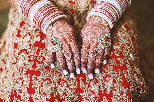 La mano della sposa indiana con il tatuaggio e i braccialetti di menhdi (henné) sul polso