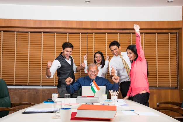 Indian business people o cultura aziendale e lavoro in ufficio concetto con laptop, documenti, riunioni che celebrano il successo o la vittoria