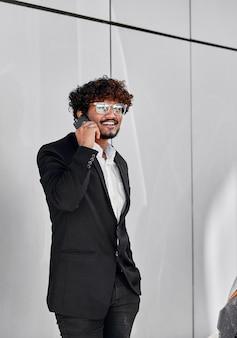 Uomo d'affari indiano con gli occhiali che parla al telefono per strada