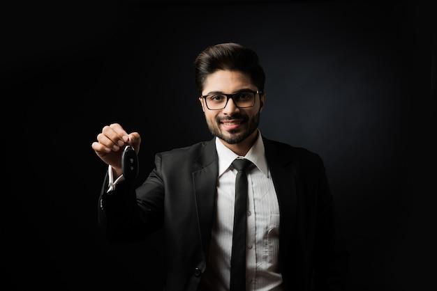 Uomo d'affari indiano con le chiavi della macchina, in piedi isolato su sfondo nero Foto Premium