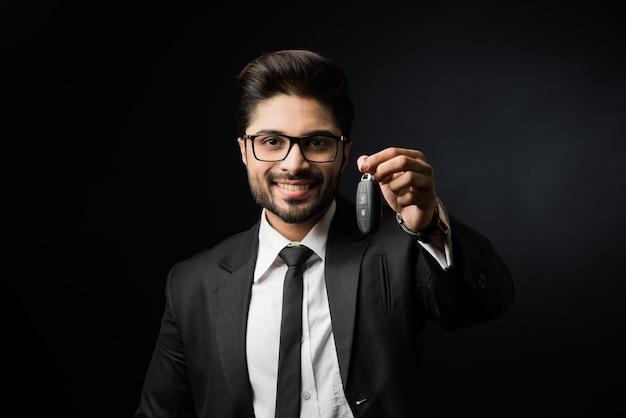 Uomo d'affari indiano con le chiavi della macchina, in piedi isolato su sfondo nero