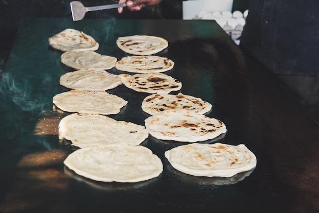 Chapatti indiano in fiamme, pushkar, india primo piano. tortillas fritte su una teglia calda. cibo di strada. naan. venditore di cibo di strada tradizionale. l'uomo cucina e inverte focacce indiane, servite con curry.