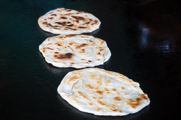 Chapatti indiano in fiamme, pushkar, india primo piano. tortillas fritte su una teglia calda. cibo di strada. naan.