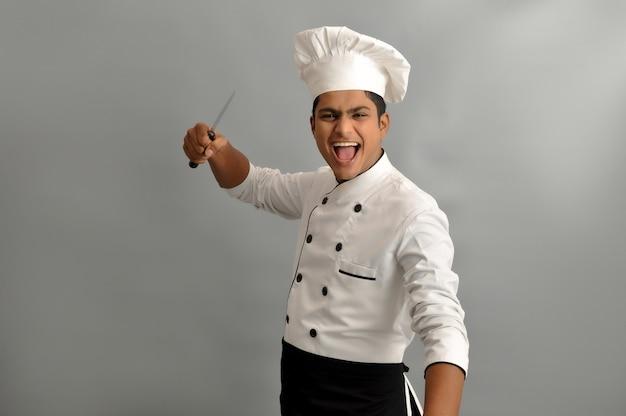 Lo chef indiano sorride e fa una posa d'azione con i suoi coltelli mentre si trova su uno sfondo grigio