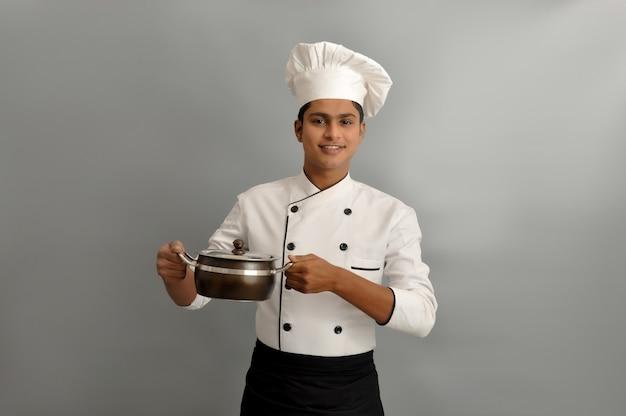 Lo chef indiano sorride e tiene in mano una pentola