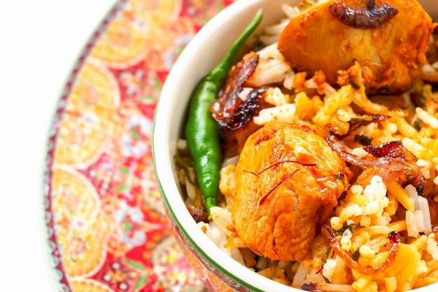 Il pollo indiano biryani è servito con il fondo di bianco di raita del pomodoro del yogurt. messa a fuoco selettiva