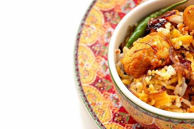 Biryani indiano del pollo con il fondo di bianco di raita del pomodoro del yogurt. messa a fuoco selettiva