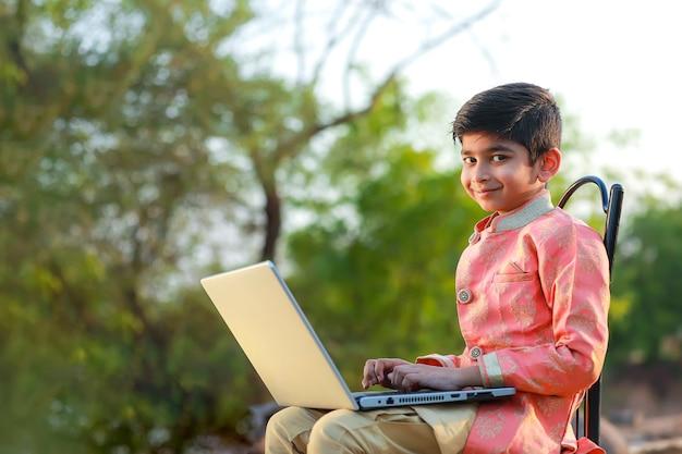 Bambino indiano che indossa un panno tradizionale e utilizzando laptop