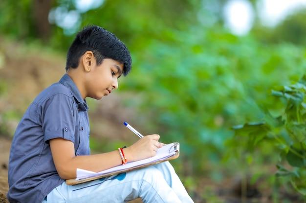 Bambino indiano che scrive sul taccuino