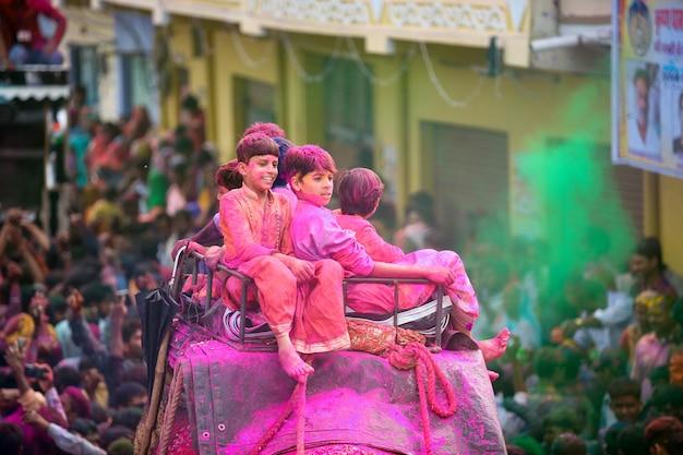 Bambini indiani che si godono il festival di holi con i colori sull'elefante