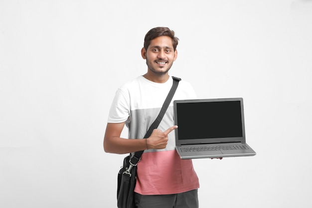 Studente di college indiano che mostra lo schermo del laptop su priorità bassa bianca.