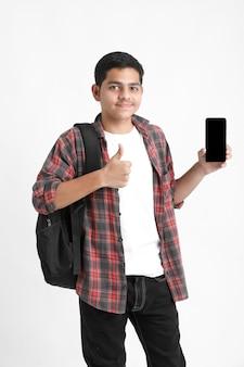 Studente di college indiano che mostra lo schermo mobile sulla parete bianca