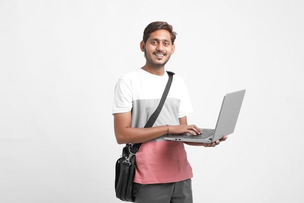 Studente di college indiano utilizzando laptop su sfondo bianco.