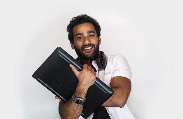 Studente di college indiano con il computer portatile su priorità bassa bianca