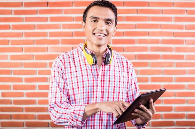 Studente di college indiano con computer tablet