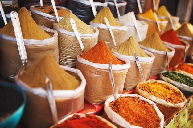 Spezie colorate indiane al mercato locale. una varietà di spezie di diversi colori e sfumature, sapori e trame sulle bancarelle del mercato indiano