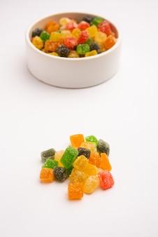 Caramelle colorate indiane e morsi di gelatina dolci al gusto di frutta ricoperti di zucchero, serviti in un piatto o in una ciotola