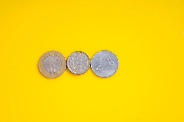 Monete in valuta indiana su sfondo giallo