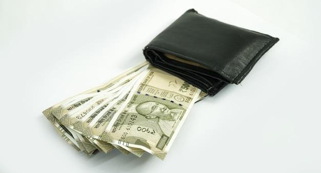 Valuta indiana con portafoglio isolato in superficie bianca