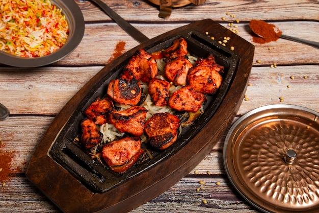 Pasto al curry indiano con piatto di pollo tandoori con contorno di cipolla