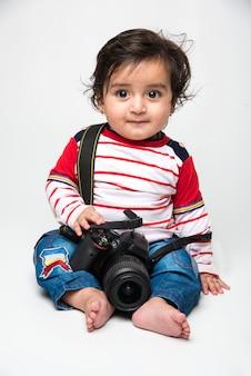 Indiano carino bambino o neonato o bambino che tiene in mano una fotocamera dslr, vuole essere un fotografo