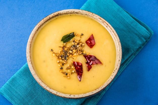 Indiano dal tadka o indiano dal tarka, dal fry, cotto dal giallo, piatto principale indiano con ricchi protine, isolato su sfondo blu