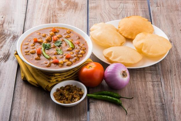 Piatto indiano piccante ceci curry noto anche come chola o chana masala o comunemente chole, servito servito con puri fritti o poveri su sfondo colorato o in legno. messa a fuoco selettiva