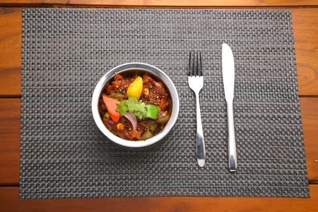 Piatto indiano veg kolhapuri piatto indiano del nord disposto in una ciotola d'acciaio