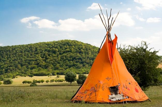Indiano etnico domicilio, teepee aka wigwam sul prato