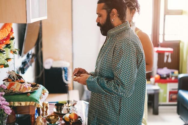 Famiglia indiana che celebra evento indù di religione a casa - culture dell'asia meridionale e concetto di stile di vita - focus sul volto dell'uomo