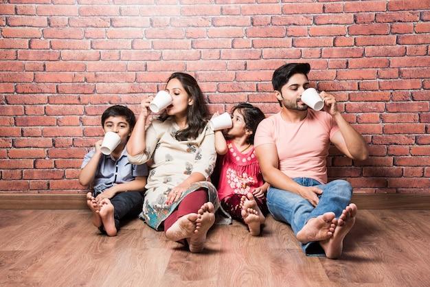 Famiglia indiana che beve latte bianco seduto sul pavimento di legno contro un muro di mattoni rossi al chiuso