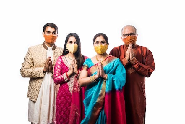 Famiglia indiana di quattro persone che indossano maschere protettive per il viso durante i festival dopo l'epidemia di coronavirus e influenza. protezione da virus e malattie, quarantena. covid-2019. isolato su sfondo bianco