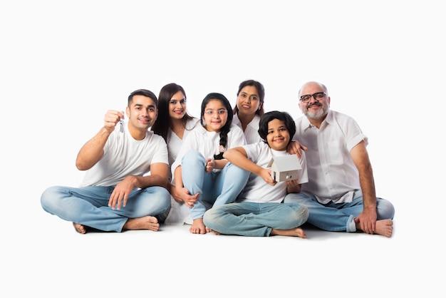 Famiglia indiana e concetto immobiliare - famiglia asiatica multigenerazionale che tiene in mano un modello di casa di carta con chiavi su sfondo bianco